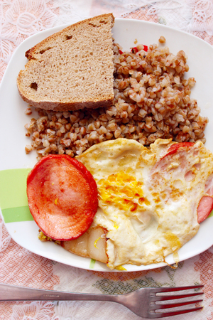 dish for a dinner from boiled buckwheat fried piece of sausage and fried eggs on the plate Stock Photo
