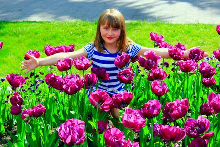 rape: hermosa niña en el macizo de flores con los tulipanes de color lila Foto de archivo