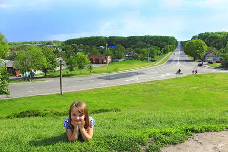 little fashionable girl lies on the green grass