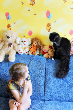 comfortableness: little girl looks at her black cat in the childrens room with toys