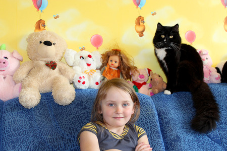 comfortableness: little girl and her black cat in the childrens room with toys