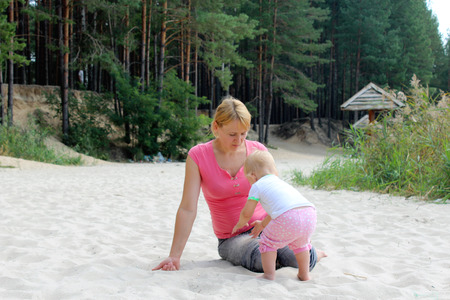 happy mother play about with her baby on the white sand Stock Photo