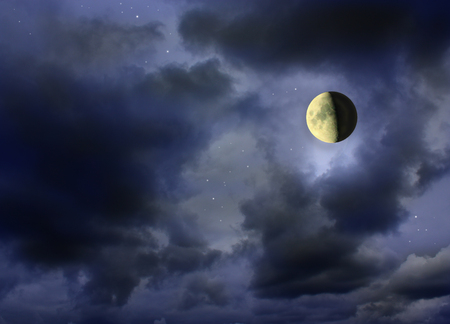starlit: Moon glowing in the dark cloudy night sky with stars.
