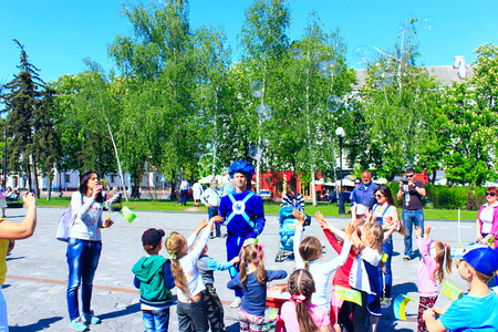 Happy children are glad of blowing bubbles. Family have a rest in the Chernihiv town in the spring Editöryel