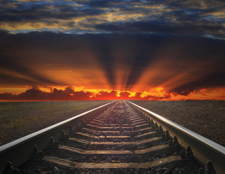 rails going away into the fiery red sunset. rails going away into the dark landscape with fiery red sunset Stock Photo