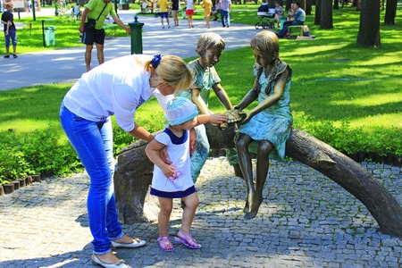 Mother with her daughter near matallic sculpture in the city park