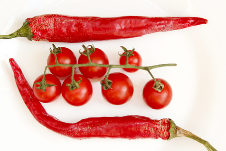 branch of red tomatoes and two pods of chili peppers isolated on the white Stock Photo