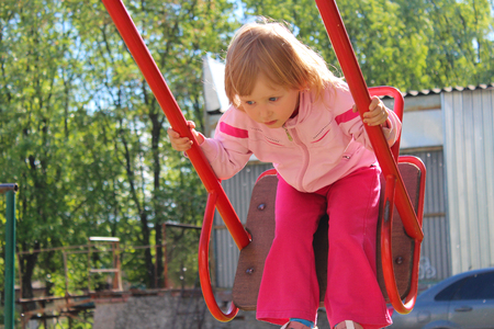 Little girl plays on the swing. Childhood the better years. Happy child