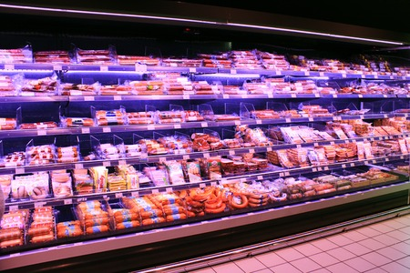 Sausages in shop. Wide choice of different sausages and meat products on shelves of shop. Sausages in shop.