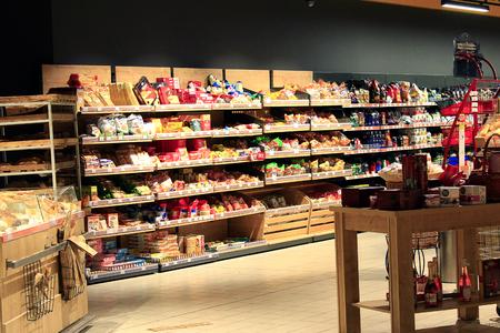Lebensmittelgeschäft mit reichhaltigem Warensortiment. Tee Kaffee Brot. Große Auswahl an verschiedenen Produktwaren in den Regalen des Supermarktes Editorial