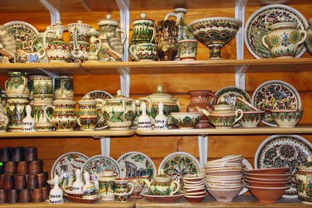 A wide choice of ceramic products on shelf of store. Pottery for sale. Ceramic goods. Products of ceramics on sale