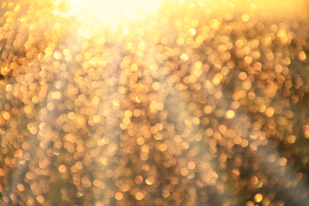 Golden bokeh. Texture with gold abstraction. Creative abstract golden patterned background. A lot of gold bokeh. Bright rays