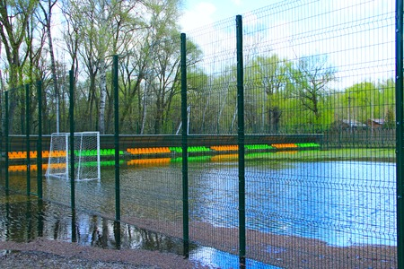 Football field during the flood of river. Small football stadium fenced with net is flooded with water during flood. Football has taken break Reklamní fotografie