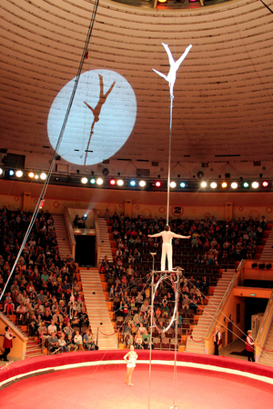 Circus number. Man equilibrist showing tricks during performance of gymnasts in circus. Gymnasts equilibrists under circus dome