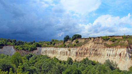 Cretaceous quarry. Landscape with sandy cliffs and beautiful sky. Cretaceous pit. Sandy cliffs with forest at foot. Sandy mountains. Celestial landscape with deposits of chalk