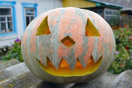 orange pumpking with cut face is ready for Halloween on rural house background. Halloween in village. Pumpkin symbol of Halloween Stock Photo