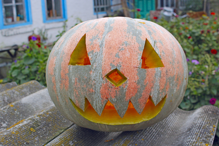 Orange pumpking with cut face is ready for Halloween on rural house background. Halloween in village. Pumpkin symbol of Halloween