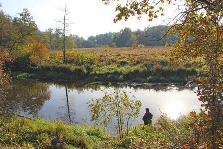 Fisherman fishing on autumn lake. Fisherman standing on riverside and trying to catch fish. Spending free time. Male hobby. Recreation. Lifestyle concept. Fisher on river bank in autumn