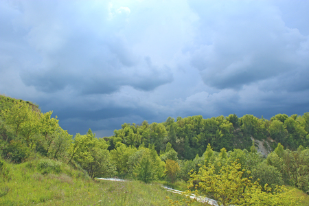 Landscape with thundercloud over green forest. Storm cloud above green vegetations. Beautiful raincloud on with dark blue clouds. Nature before rain. Rainy clouds before downpour Stock Photo