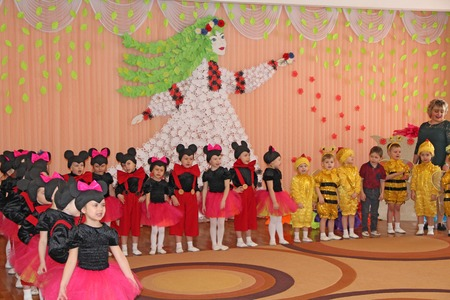 Children in costumes of bees and Mickey Mouse in matinee at kindergarten. Joyful children during performance in kindergarten