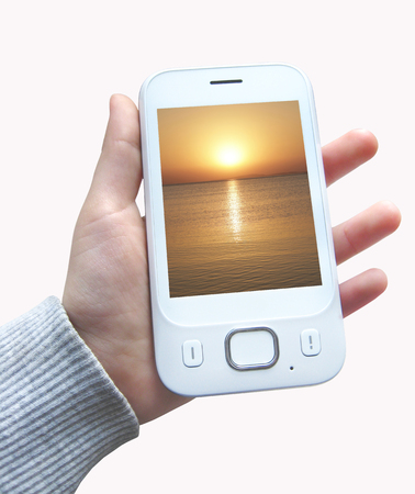 Modern smartphone with image of sunset above ocean on screen in hand isolated on white background. Mobile phone in human hand isolated. Modern communications