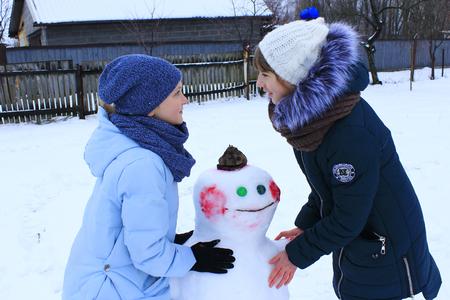 Two girls make snowman in winter. Children make snowman. Two sisters make snowman in winter day Banque d'images - 113682436