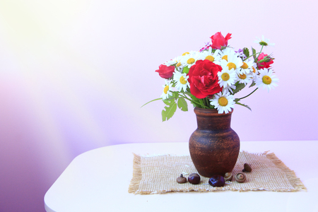 Bouquet of white daisies and red roses in clay pot is on sacking. Flowers in pot on lilac background. Chamomiles and red roses in vase on table Stock fotó
