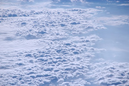 Beautiful view from window of plane over white clouds. Wonderful view from window of plane to white clouds flying down. Beautiful white clouds. Landscape with heaven. Heaven panorama