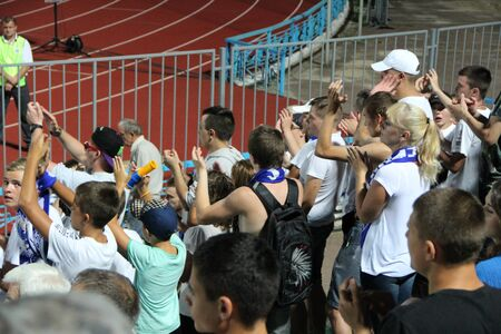 football fans of Desna Chernihiv support team during match. Young people are fans of Ukrainian football club Desna Chernihiv