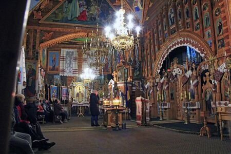Beautiful interior and decoration in Orthodox church. People praying inside of church during service. Редакционное