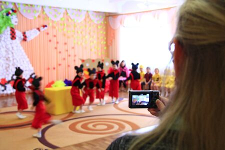 Woman taking video of childrens morning party. Children on matinee at kindergarten. Woma making video on camera in kindergarten during festive performing. Childish show Editorial