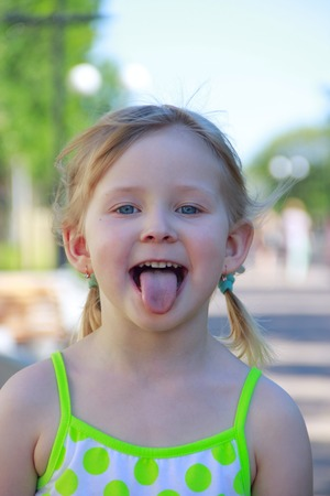 Little girl smiling and showing tongue. Face expression. Childish emotions. Childish face with funny grimace. Pirtrait of having fun girl