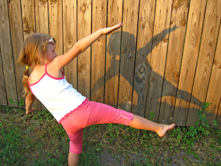Little girl dabbling and watching shadow on fence. Child looking at her shadow on wooden fence. Little girl making figures from shadow on wooden fence background