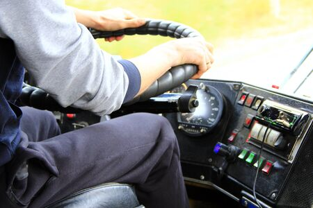 Driver is driving bus. Driver switches gear lever in bus. Dashboard in the bus
