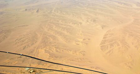 Beautiful view onto asphalt road in wild sandy lands of desert. Aerial scenery view of highway passing through desert. Drone shot from above of desert landscape with highway.