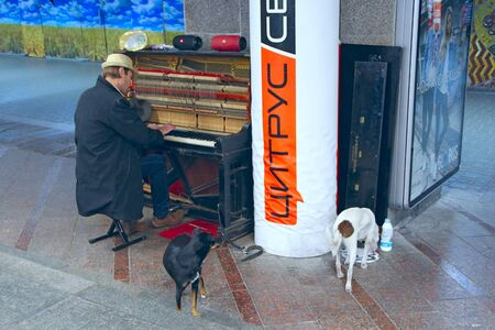 Homeless man playing piano on street surrounded by stray dogs. Musician playing piano outdoors. Pianist earning his living by playing with piano