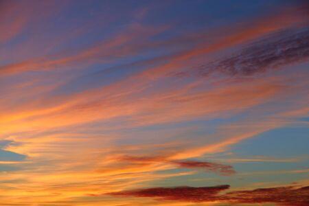 Orange sunset before night. Orange sky at sunset. Twilight with bright sunset. Sunny rays leaving with decline. Evening landscape Фото со стока