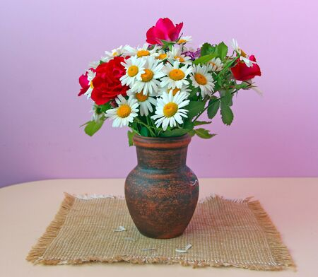 Bouquet of white daisies and red roses in clay pot is on sacking. Flowers in pot on lilac background. Chamomiles and red roses in vase on table Stok Fotoğraf