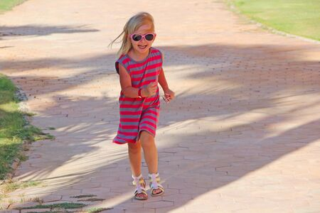 Happy little girl running on country road. Positive childish emitions. Child running along path smiling and rejoicing. Happy childhood. Little girl running along city park