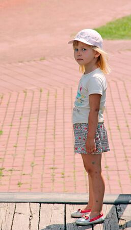 Offended girl standing on street. Sad child standing in street. Upset girl silently standing on street. Banque d'images - 131691310