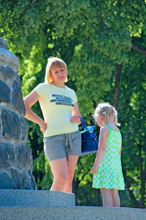 Mom scolding daughter for naughty behavior outside. Mother scolding girl. Baby behavior outside. Naughty baby punished by mom