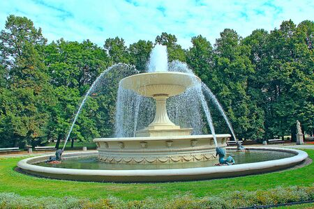 Large fountain in bowl in city park of Warsaw. Beautiful fountain in park of Warsaw. Huge bowl with fountain in summer park