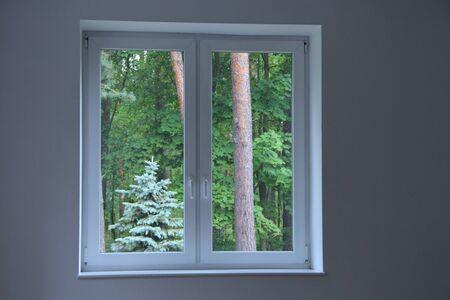 grande fenêtre donnant sur forêt dans chambre claire. Fenêtre avec vue sur la forêt verte. Chambre dans maison de campagne avec vue sur la forêt
