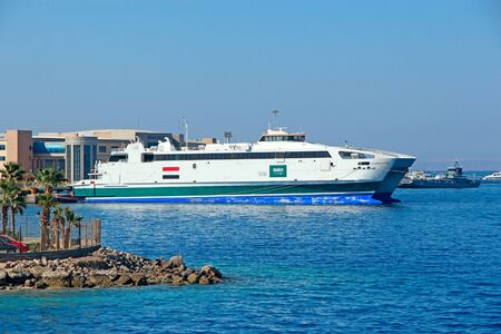 Cruise liner with tourists sailing on Red Sea. Sea voyage on white boat. Cruise ship with tourists on Sea. Mass tourism on sea