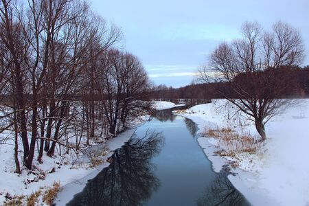 Beautiful landscape with winter river and forest. Winter river surrounded by trees. Winter forest on river. Landscape with snowy trees. Beautiful non-freezing river in frost