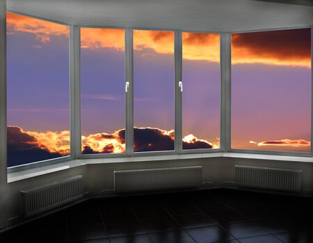 Plastic windows overlooking beautiful decline. View from home window at sunset. Sunset outside window. Window view of sky with bright sunset. View from window of room on evening sky with fiery sunset