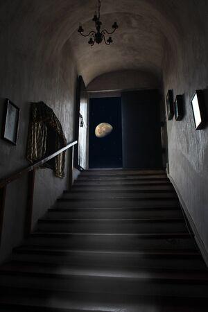 Exit dungeon upstairs overlooking starry sky and moon. Magical view of moon from dark room. Doorway in basement overlooking night sky 스톡 콘텐츠