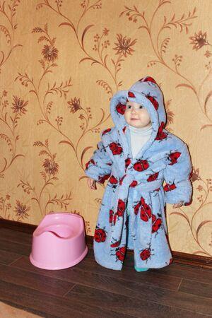Funny baby in bathrobe near potty. Little girl smiling standing near children potty. Little toddler baby kid girl standing by plastic potty. Toilet training
