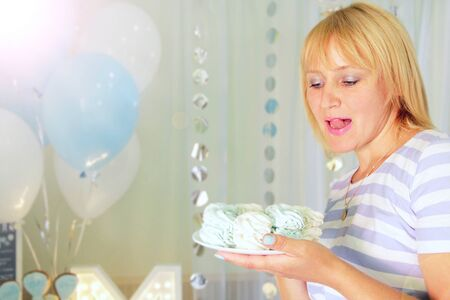 Beautiful woman biting tongue looking at holiday cake. Attractive woman looking at delicious biscuit cake. Young woman going to eat festive Meringue cake. Girl enjoying sweet food