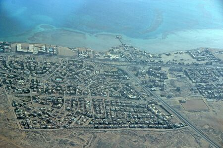 Aerial city view with houses, buildings, seaside in Egypt. Flying above country. Panoramic image. Egyptian town seen from above. Egyptial town from sky. Aerial panorama of town on seaside 스톡 콘텐츠